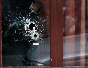 epa05024526 A man looks outside the Carillon cafe with bullets holes on the glasses, in Paris, France, 14 November 2015. At least 120 people have been killed in a series of attacks in Paris on 13 November, according to French officials. Eight assailants were killed, seven when they detonated their explosive belts, and one when he was shot by officers, police said. French President Francois Hollande says that the attacks in Paris were an 'act of war' carried out by the Islamic State extremist group.  EPA/YOAN VALAT