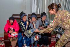 Foto 2 - militare italiano consegna i vestiti ai bambini